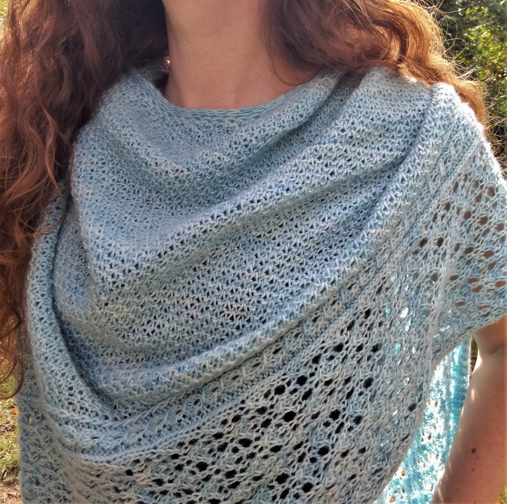 A richly textured, icy blue shawl with a lace border is draped around a person's neck. The person is standing outdoors on a sunny day.