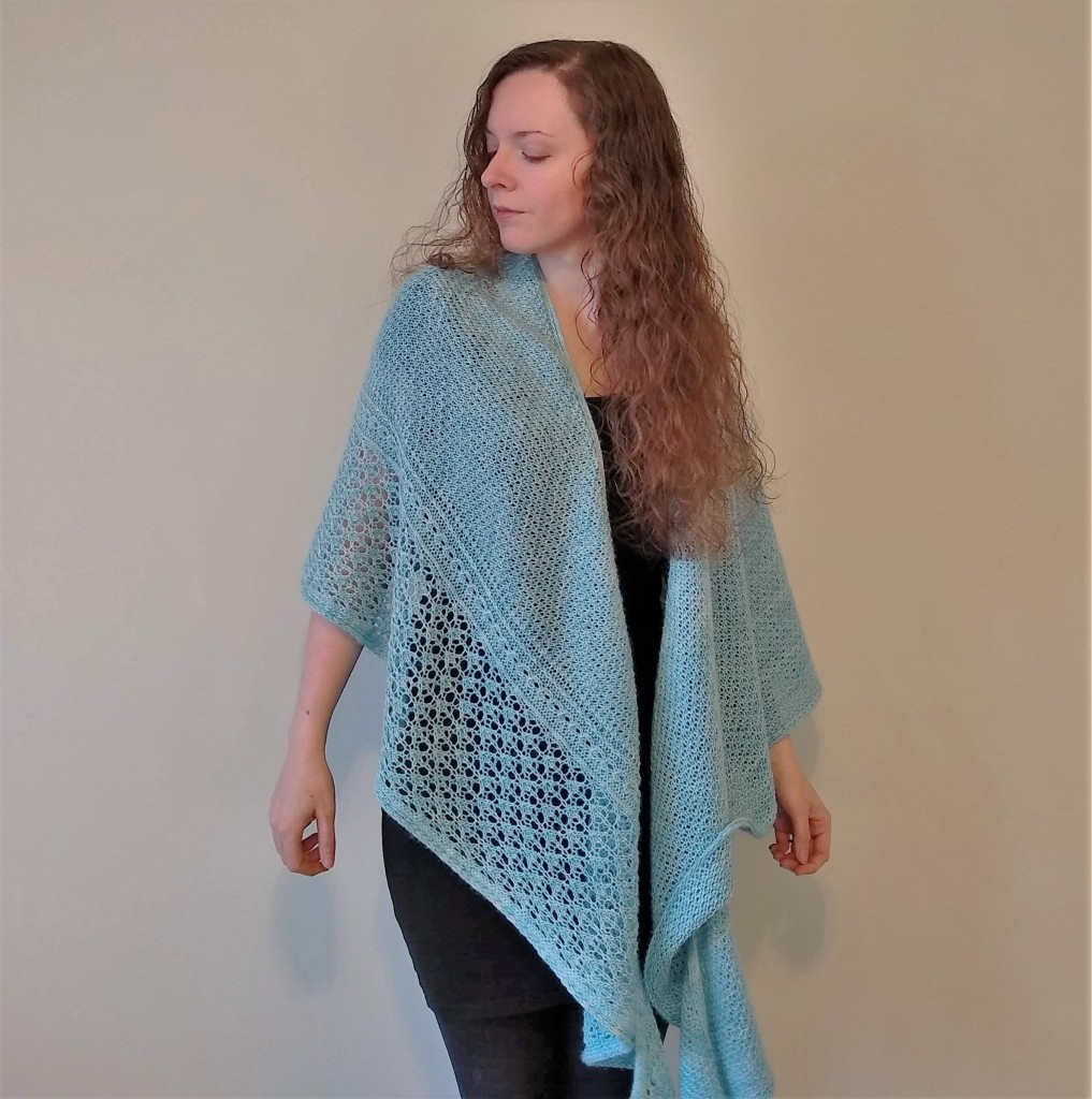 A large and richly textured icy blue shawl with a lace border is draped around a woman's shoulders.