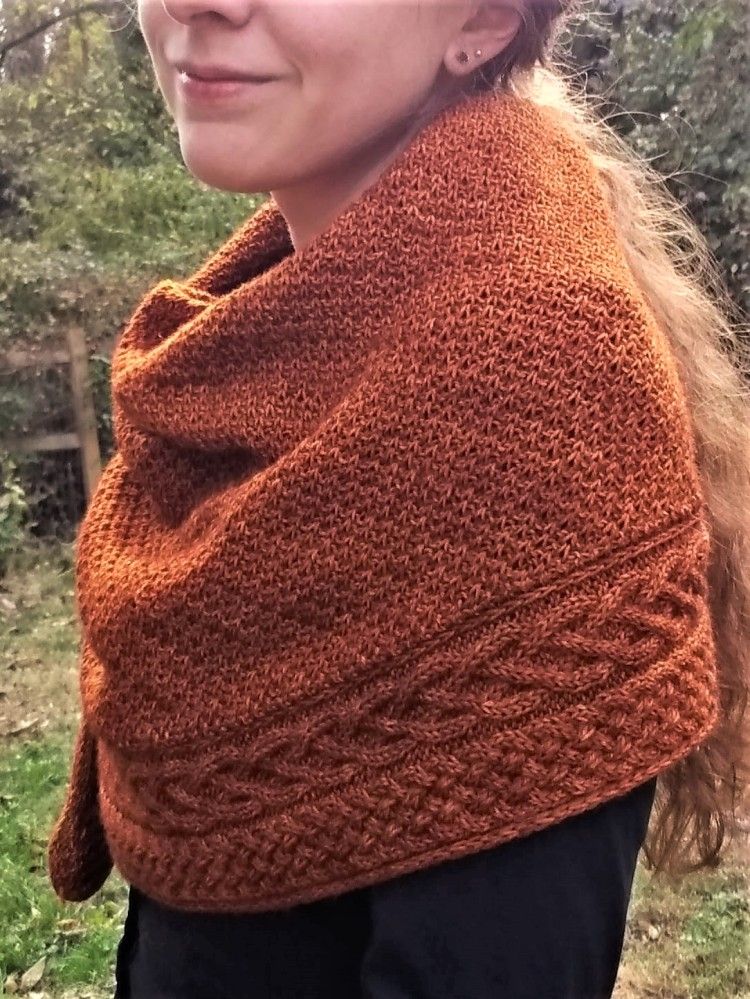 A woman wears a copper colored, richly textured shawl with two intricate cables running along the bottom draped around her shoulders.