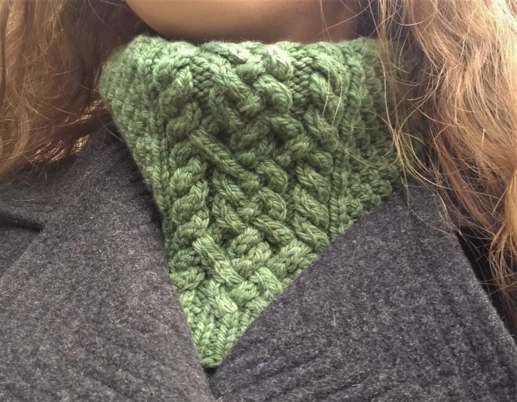 A green cowl with intricate cables worn around a person's neck.