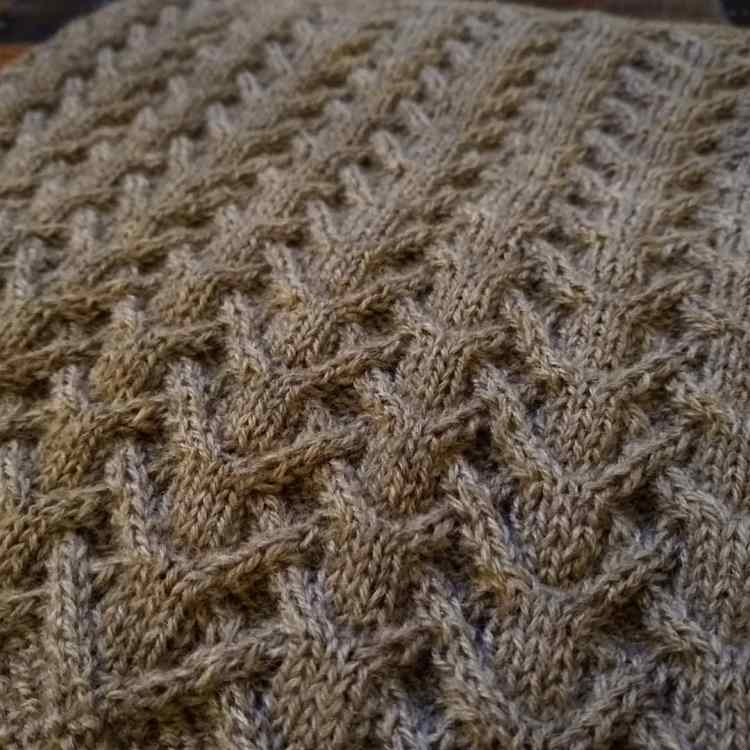 A close-up of the interlacing cables on a cowl knit in a soft, warm gray yarn.