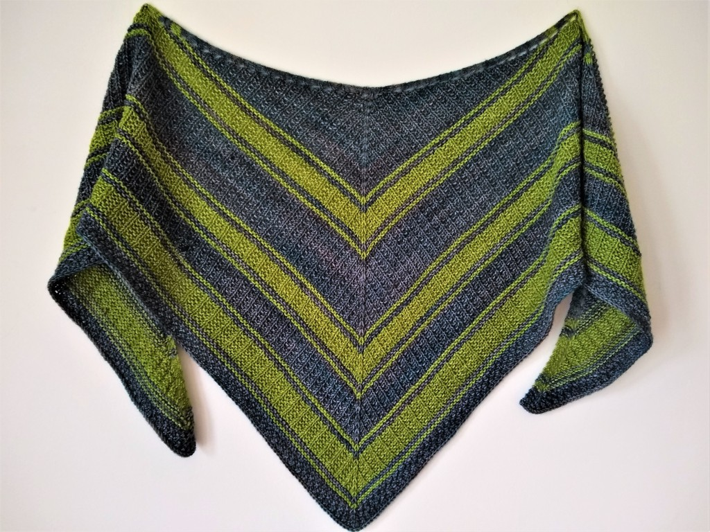 A textured triangular shawl with wide blue and green stripes hangs on a white wall.