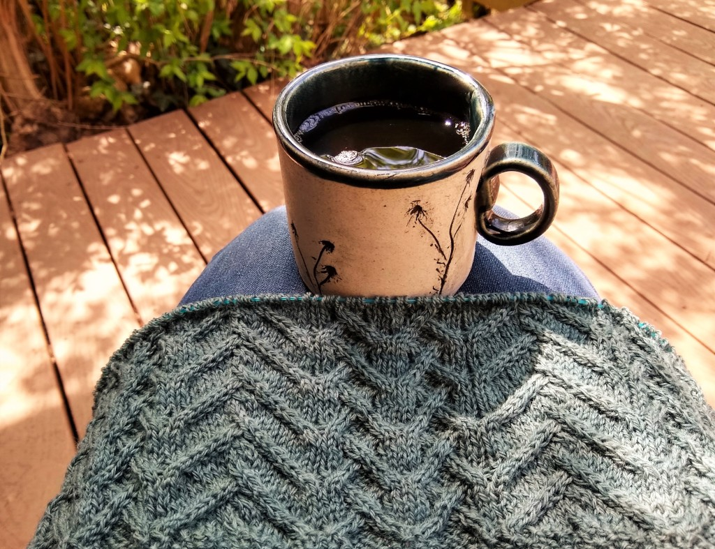 A blue, heavily cabled wrap in progress and a mug decorated with wildflower imprints are balanced on a person's lap.